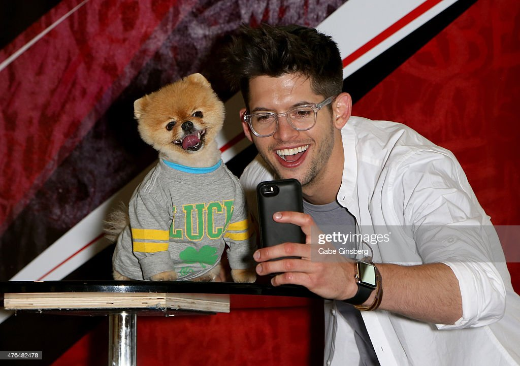 Jiff (L), the world's fastest dog on two paws, and actor Hunter March take a selfie as they attend the Licensing Expo 2015 at the Mandalay Bay Convention Center on June 9, 2015 in Las Vegas, Nevada.