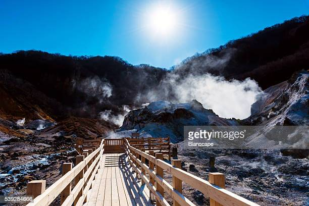 Jigokudani or Hell Valley against sunrise and sky with wooden footpath in Noboribetsu, Hokkaido