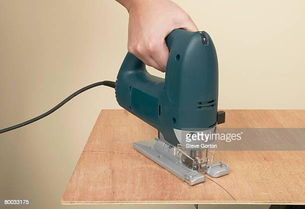 Jigsaw cutting through wood