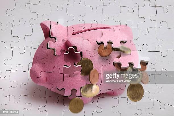 Jigsaw piggy bank falling apart spilling money