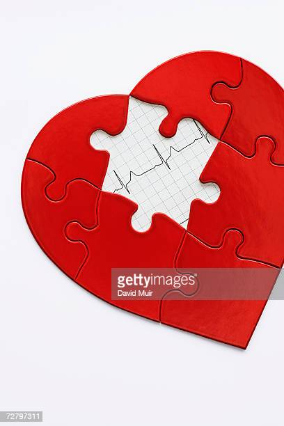 Jigsaw puzzle in heart shape, missing piece revealing EKG printout,, close-up