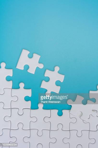 jigsaw puzzle on blue background - raadsel stockfoto's en -beelden