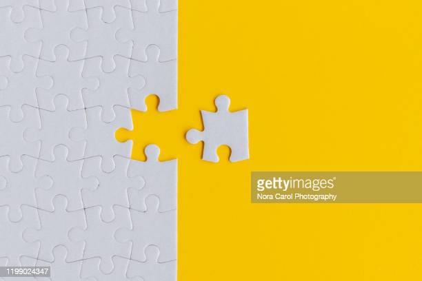 jigsaw puzzle on yellow background - the end stock pictures, royalty-free photos & images