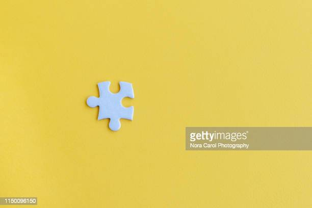 jigsaw puzzle piece on yellow backgrounds - jigsaw piece stock pictures, royalty-free photos & images