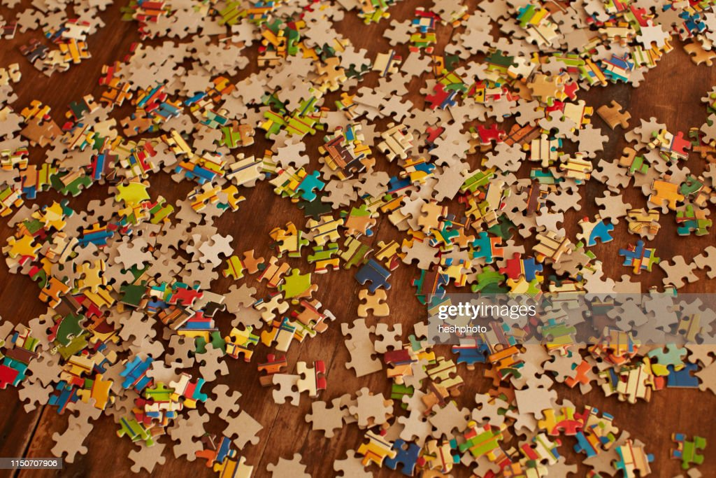 Jigsaw puzzle pieces on wooden floor : Stock Photo