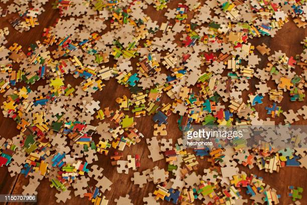 jigsaw puzzle pieces on wooden floor - heshphoto stock pictures, royalty-free photos & images