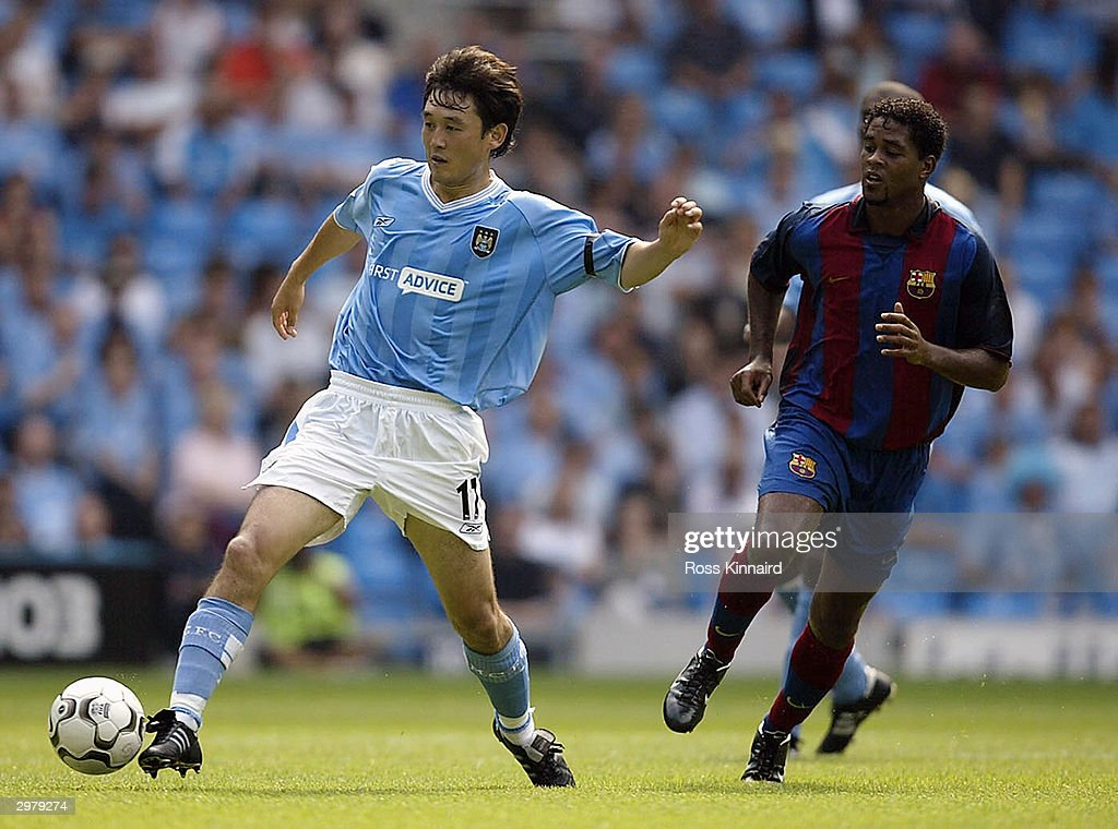 Jihai Sun of Manchester City goes past Patrick Kluivert of Barcelona during the pre season friendly match on August 10, 2003 at the City of Manchester Stadium, Manchester, England. (Photo by Ross KInnaird/Getty Images).