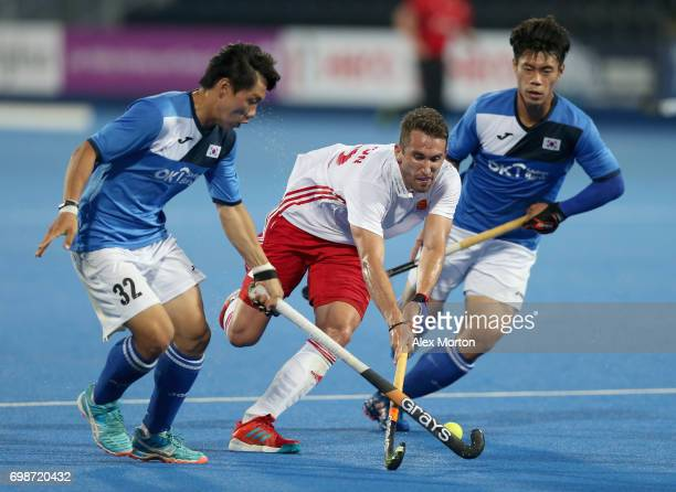 Jihun Yang of South Korea and Hoon Kim Ki of South Korea attempt to tackle David Condon of England during the Pool B match between India and the...