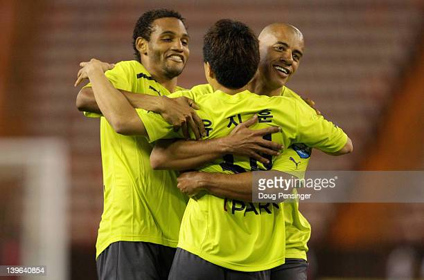 Jihun Yu of Busan I'Park FC of Korea is congratulated by teammates Eder Luis Carvalho and Hose Roberto Rodrigues Mota Junior after Yu kicked the game...