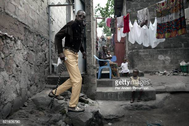 Jika, a senior Sapeur shows one of his designer outfits close to his home in the Mombele area on February 12, 2012 in Kinshasa, DRC. Jika loves...