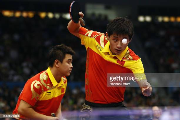 Jike Zhang of China serves in the Men's Doubles Final with Hao Wang of China against Lin Ma and Xin Xu of China at Guangzhou Gymnasium during day...