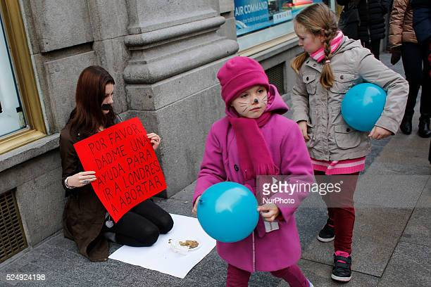 Jil Love activist and artist holds a banner where it is written 'help me go to London to have an abortion' while little children carrying ballons...