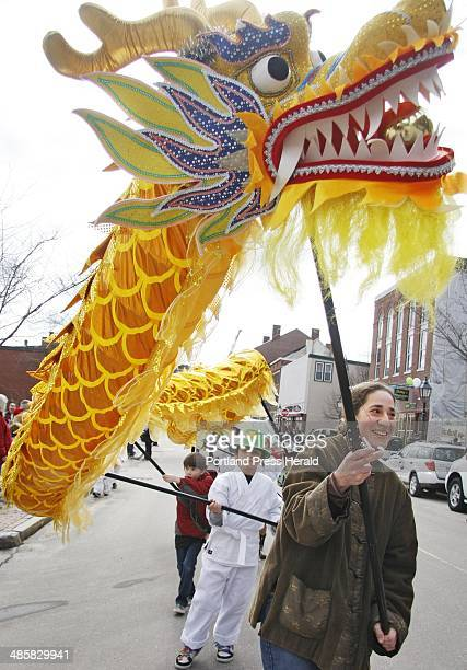Alysha Carabetta of West Bath carries a colorful dragon down Front Street with members of Five Elements Mountain School of Martial Arts during the...