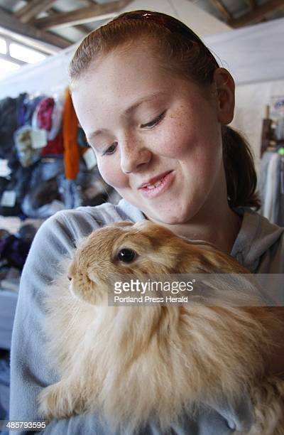 Evelyn Townsend of Fairfield snuggles with a French/German angora rabbit while visiting the Underhill Fiber Farm of Gorham booth at the Maine Fiber...