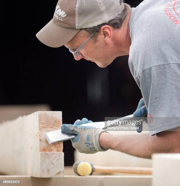 Jon Courtney cleans up a cut on a Hemlock timber while framing in a floor in the dairy barn at Broadturn Farm in Scarborough on Wednesday June 18 2008