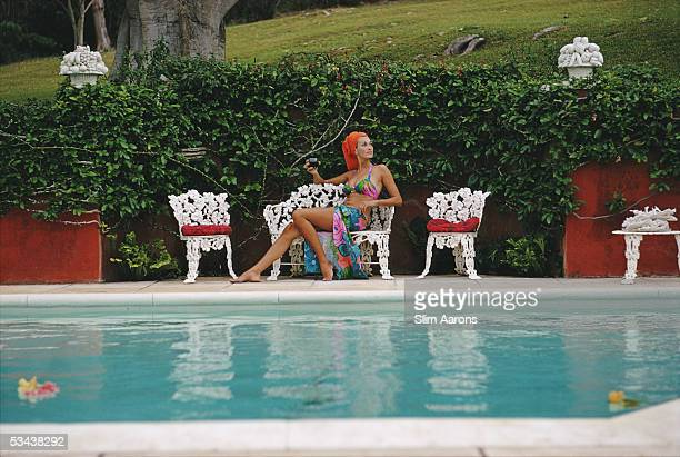 Jill Council relaxes with a drink by a swimming pool in Bermuda 1969