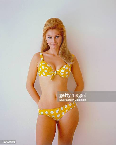 Jill Ireland , British actress, wearing a yellow polka dot bikini in a studio portrait, against a white background, circa 1960.
