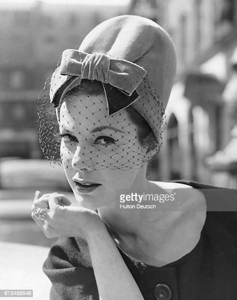 Jill Leslie models a flamingocolored velvet pillbox hat with net veil from Christian Dior's autumn collection June 1960