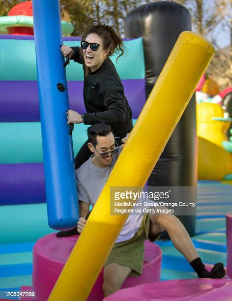 Jill McArthur, 30 and Donn Nguyen of Garden Grove enjoy a friendly jousting match at The Big Bounce America traveling playground.