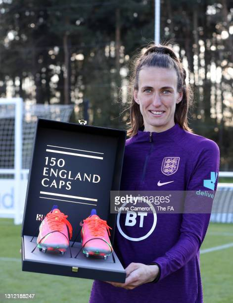 Jill Scott of England poses for a photo after being presented with a pair of boots to mark her 150th appearance after an England Training Session in...