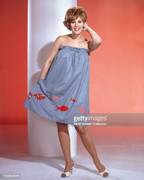 Jill St John US actress poses wearing a blue strapless dress decorated with applique fish in a studio portrait against a red background circa 1960