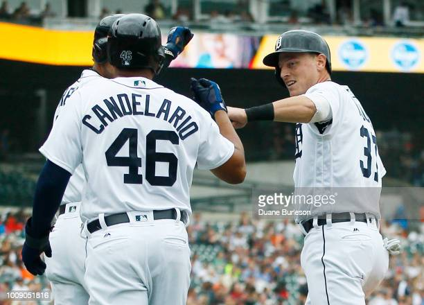 Jim Adduci of the Detroit Tigers celebrates with Jeimer Candelario after they scored against the Cincinnati Reds on a double by Jose Iglesias during...