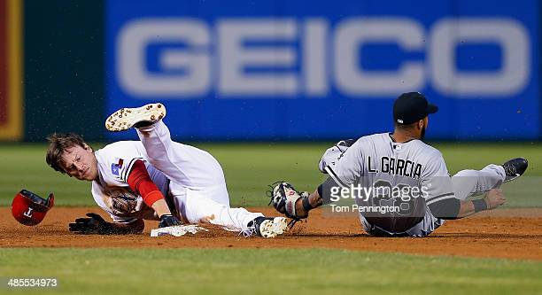 Jim Adduci of the Texas Rangers collides with Leury Garcia of the Chicago White Sox at second base in the bottom of the third inning at Globe Life...