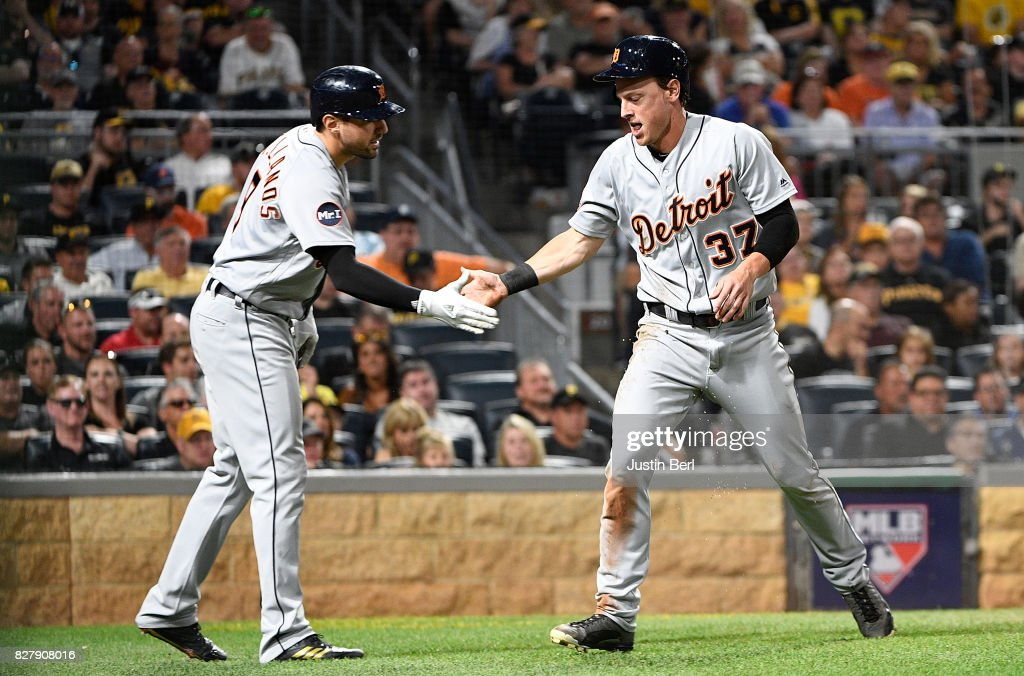 Jim Aducci #37 of the Detroit Tigers is met by Nicholas Castellanos #9 after coming around to score on an sacrifice fly ball by Miguel Cabrera #24 in the sixth inning during the game against the Pittsburgh Pirates at PNC Park on August 8, 2017 in Pittsburgh, Pennsylvania.