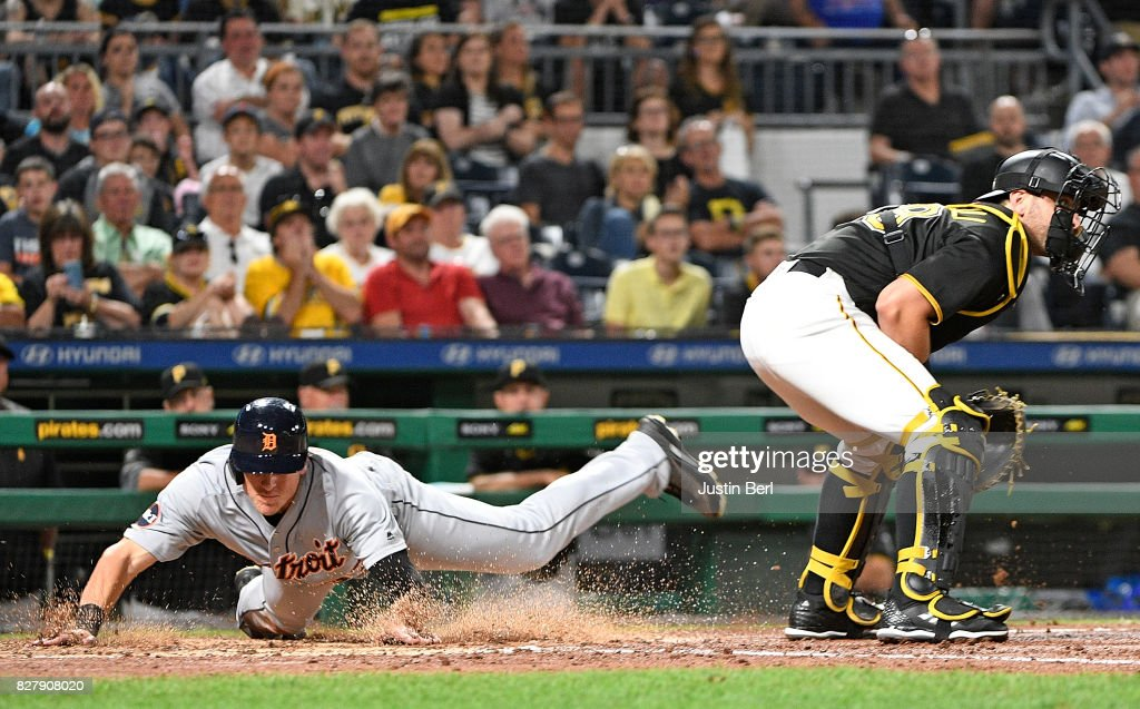 Jim Aducci #37 of the Detroit Tigers slides safely past Francisco Cervelli #29 of the Pittsburgh Pirates to score on a sacrifice fly ball by Miguel Cabrera #24 in the sixth inning during the game at PNC Park on August 8, 2017 in Pittsburgh, Pennsylvania.