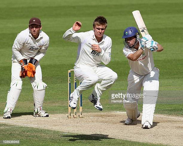 Jim Allenby of Glamorgan drives as Jason Roy of Surrey jumps clear and Gary Wilson of Surrey looks on during day three of the LV County Championship...