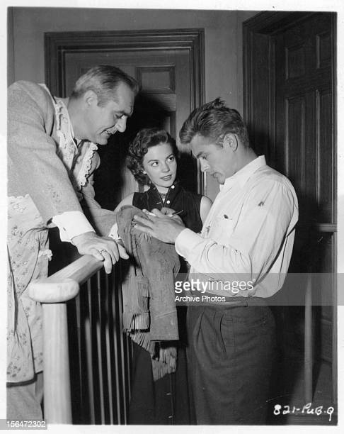 Jim Backus and Natalie Wood watch as James Dean autographs a jacket during a break from shooting the film 'Rebel Without A Cause' 1955