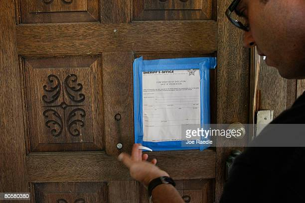 Jim Banford from Real Estate Asset Disposition corp looks at the Sheriffs eviction notice posted on the front door of the foreclosed property his...