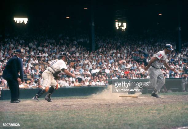 Jim Baxes of the Cleveland Indians runs towards first base as catcher Lou Berberet of the Detroit Tigers follows the play during an MLB game on July...