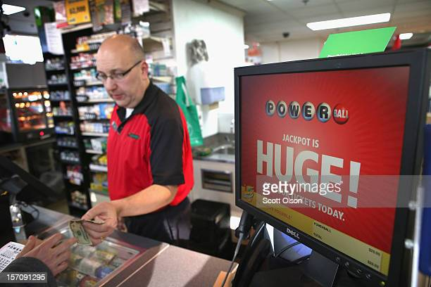 Jim Bayci sells a Powerball lottery ticket at his 7Eleven store on November 28 2012 in Chicago Illinois Bayci estimates more than half of his...