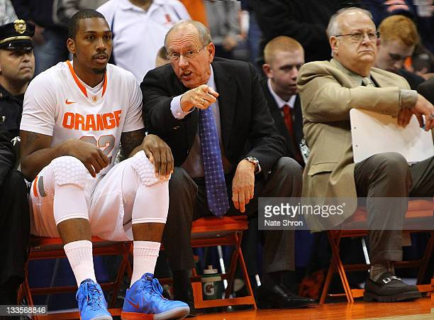 Jim Boeheim head coach of the Syracuse Orange talks with player Fab Melo on the bench as he sits next to associate head coach Bernie Fine during the...