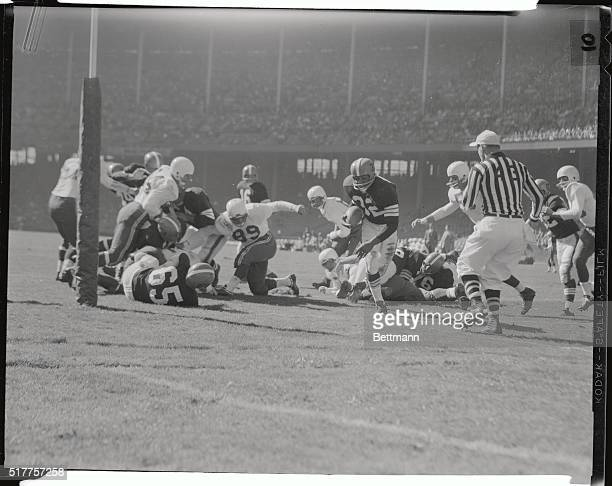 Jim Brown Cleveland Browns fullback eludes two Chicago Cardinal tacklers as he gains eleven yards in the second quarter of BrownsCards action Brown...