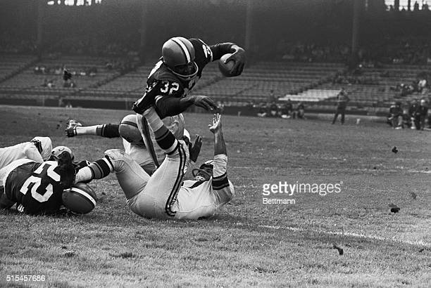 Jim Brown, Cleveland Browns fullback, goes diving over for a touchdown in third quarter on a three yard jaunt. Attempting to stop Brown are Steelers'...