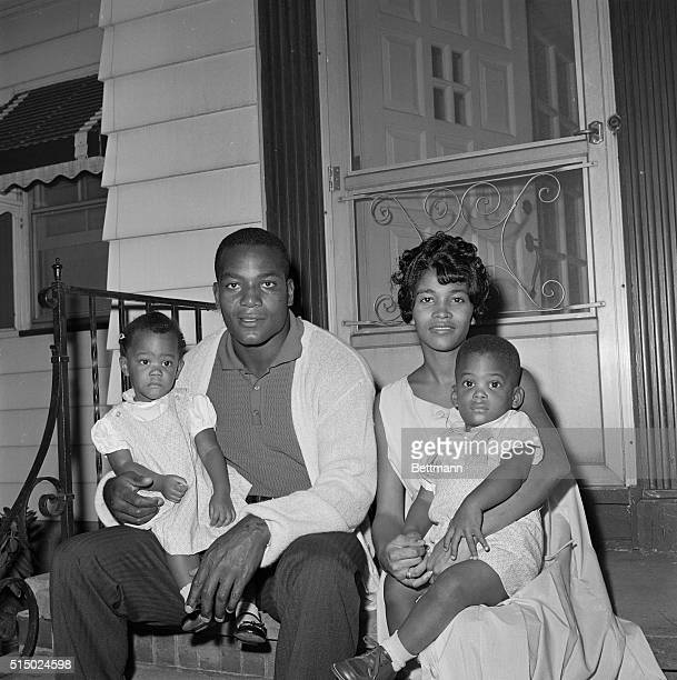Jim Brown fullback of Cleveland Browns sits in front of his home with family wife Sue and twins Kim and Kevin 19monthsold