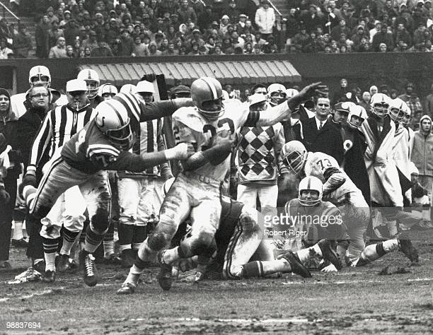 Jim Brown of the Cleveland Browns carries the ball against Billy Ray Smith Sr #74 of the Baltimore Colts as Bobby Boyd and Monte Clark look on during...