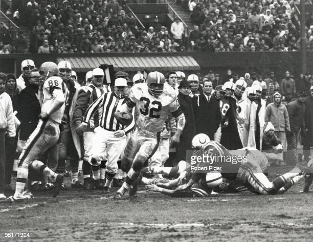 Jim Brown of the Cleveland Browns carries the ball against the Baltimore Colts during the 1964 NFL Championship game at Cleveland Stadium on December...