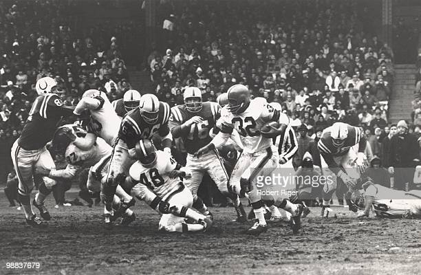 Jim Brown of the Cleveland Browns carries the ball as Dick Schafrath Johnny Brewer and Ernie Green block against Ordell Braase Don Shinnick and Fred...