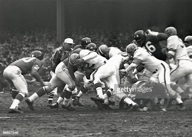 Jim Brown of the Cleveland Browns carries the ball as Gene Hickerson Jim Ray Smith and Art Hunter block against Jimmy Patton Dick Modzelewski Sam...