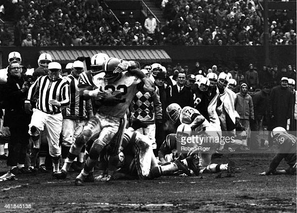 Jim Brown of the Cleveland Browns carries the ball as he is tackled by Billy Ray Smith Sr #74 of the Baltimore Colts during the 1964 NFL Championship...