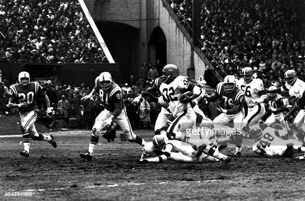 Jim Brown of the Cleveland Browns carries the ball as Ordell Braase and Jerry Logan of the Baltimore Colts persue him during the 1964 NFL...