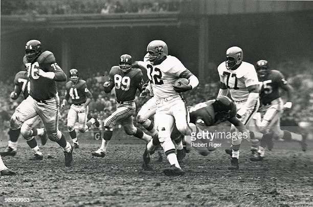 Jim Brown of the Cleveland Browns carries the ball as Willie Davis blocks and Rosie Grier and Cliff Livingston of the New York Giants pursue during a...
