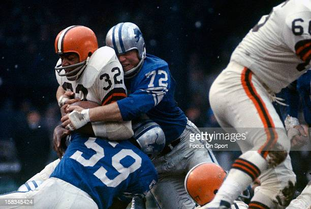 Jim Brown of the Cleveland Browns gets tackled by Ernie Clark and Floyd Peters of the Detroit Lions during an NFL football game December 8 1963 at...