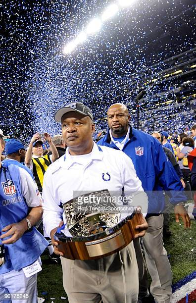 Jim Caldwell Head coach of the Indianapolis Colts walks off the field with the Lamar Hunt Trophy after defeating the New York Jets during the AFC...