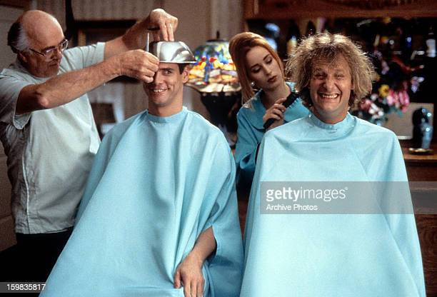 Jim Carrey and Jeff Daniels getting their hair cut in a scene from the film 'Dumb Dumber' 1994