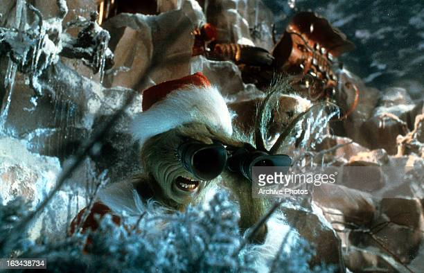 Jim Carrey looking through binoculars in a scene from the film 'How The Grinch Stole Christmas' 2000