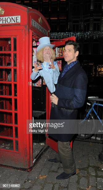 Jim Carrey poses with his puppet Harry Dunne from Dumb and Dumber inside a London telephone box covered in call girl advertising after dining at Zuma...